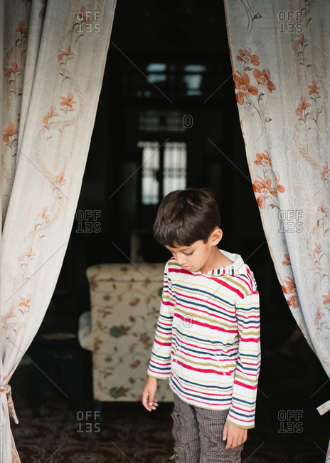 Young boy standing in curtained doorway of home