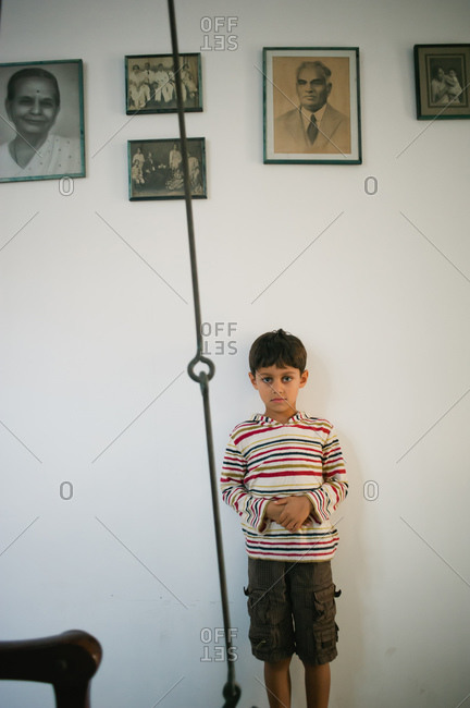Boy standing against wall with photos of his relatives