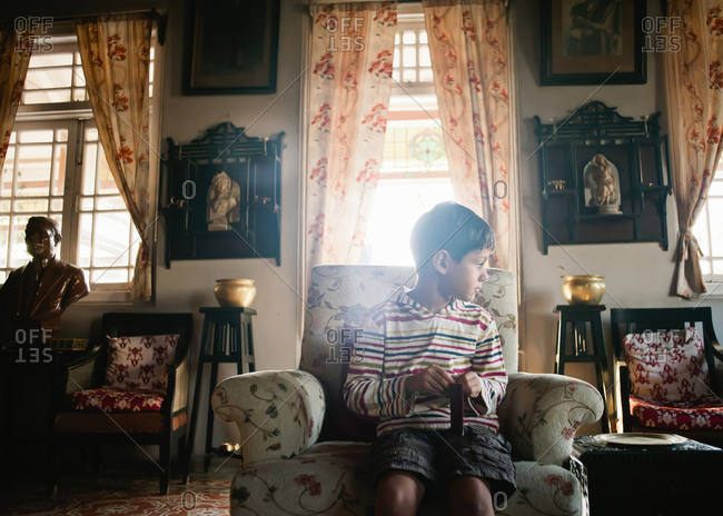 Boy sitting on chair in ornately decorated living room
