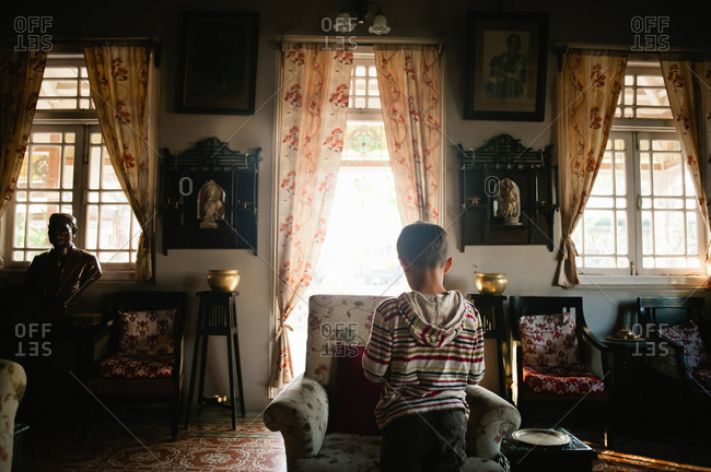 Boy standing in ornately decorated living room