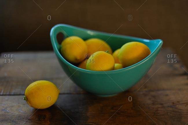 Still life of bowl of lemons on wooden table