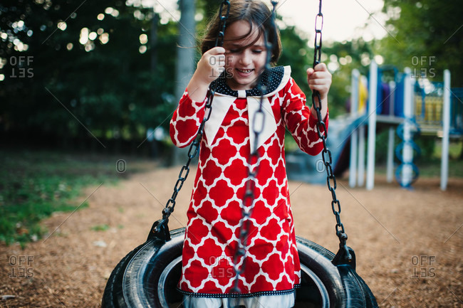 Young girl in a red and white patterned dress on tire swing