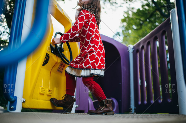 Girl in red dress playing on at steering wheel on jungle gym