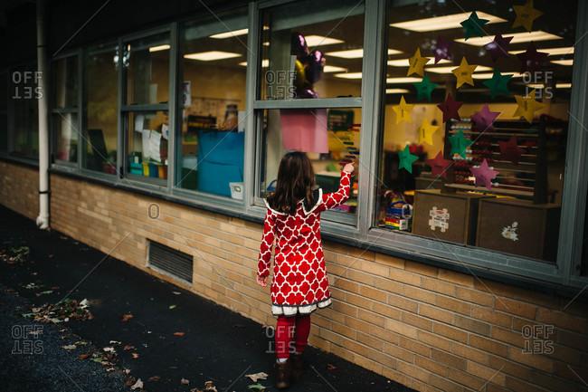 Girl gazing through school window