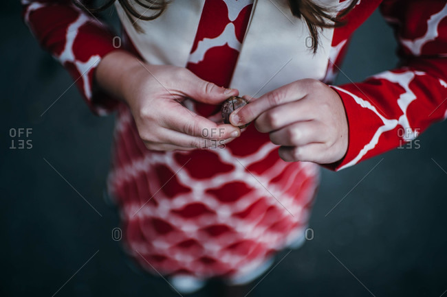 Overhead view of girl in red dress holding an acorn