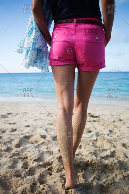 A woman in pink shorts walks on the beach