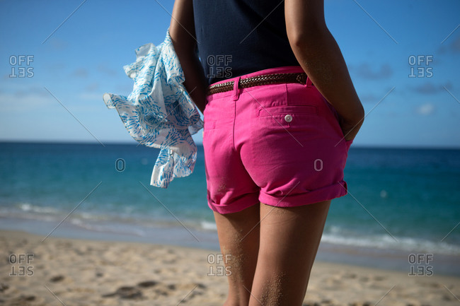 A woman in pink shorts stands on the beach