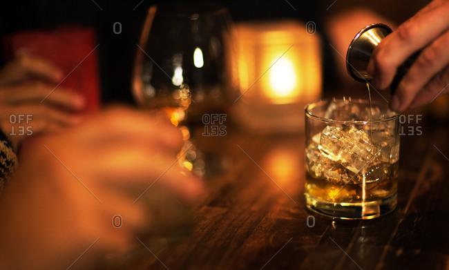 A bartender pours liquor in a dimly lit bar