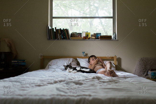 Young boy in underpants lying in bed with cat