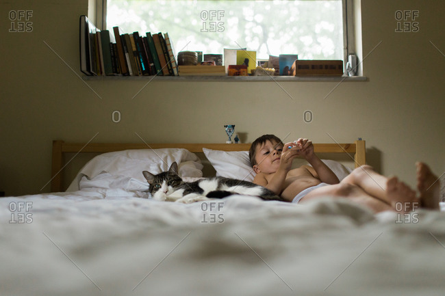 A boy lays on his bed with his cat