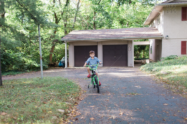 Young boy riding bike down driveway