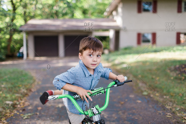 Young boy getting off bicycle