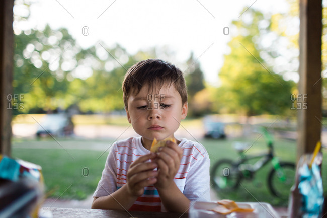 Little boy eating lunch at the park
