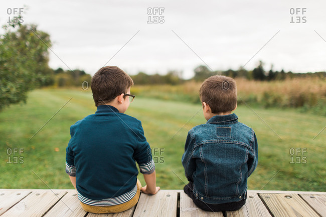 Two brothers sitting on wooden deck