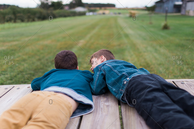 Two brothers lying on wooden deck