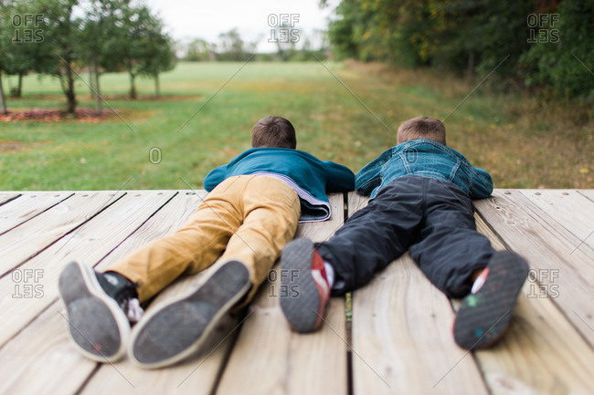 Full body image of two brothers lying on wooden deck