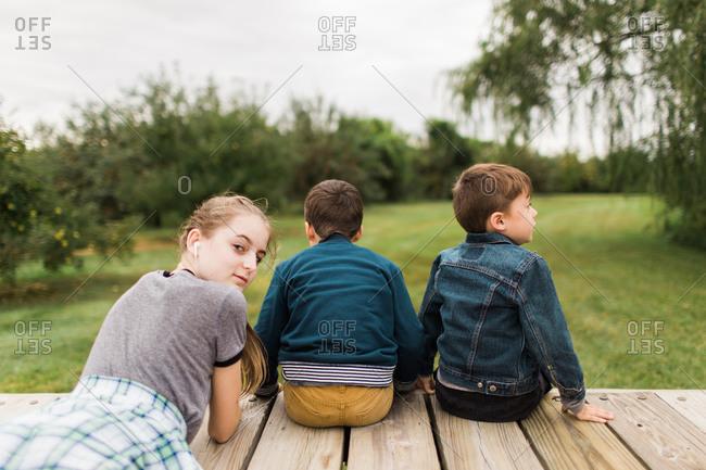 Three children on a back porch