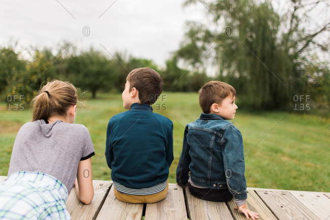 Two brothers and sister sitting on wooden deck