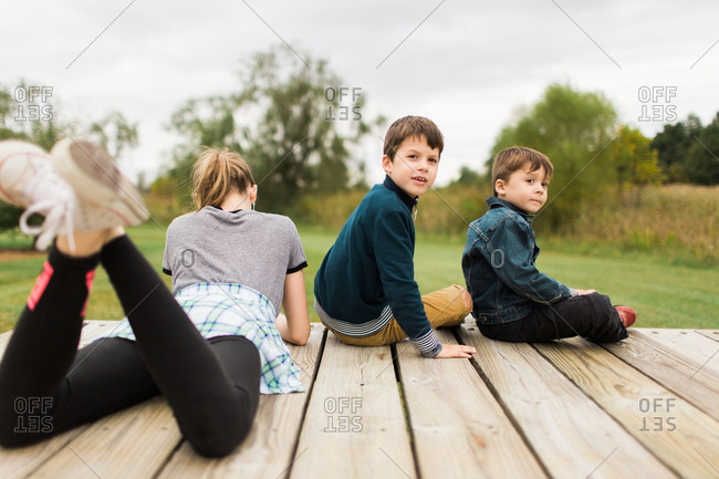 Two brothers turned around and sister sitting on wooden deck