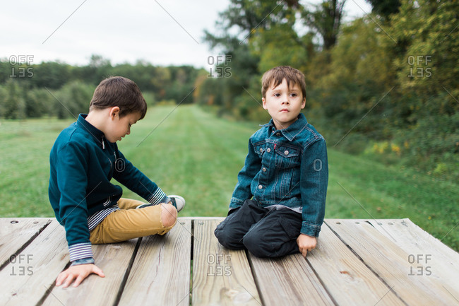 Two brothers sitting on wooden deck together
