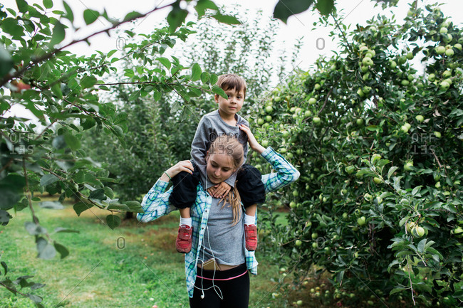 Sister carrying little brother through orchard