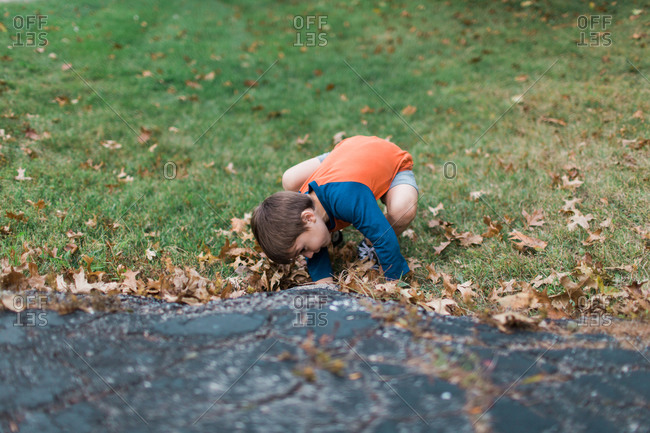 Young boy crouched on grass to look under bump in pavement