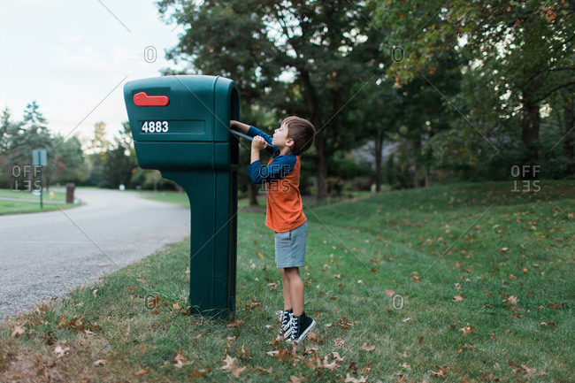 Boy on his tiptoes to retrieve mail from mailbox