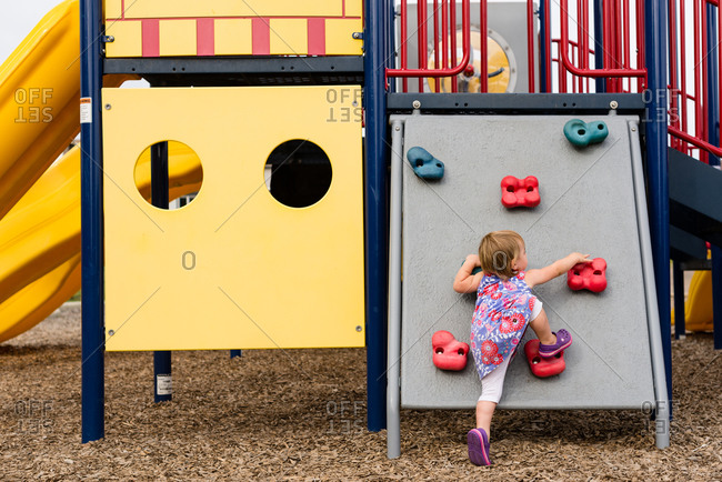 A toddler girl plays in a playground