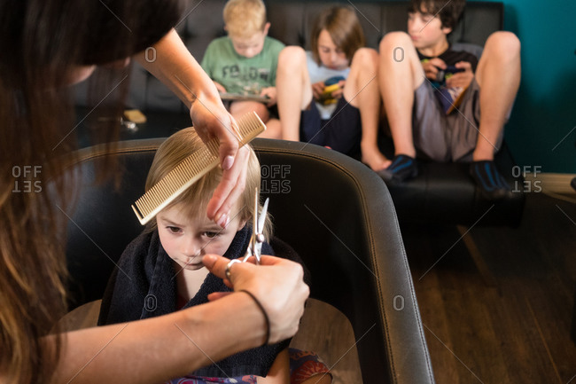 A toddler gets her hair cut while her brothers wait