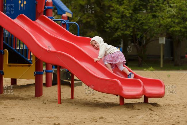A little girl climbs up a slide at a playground