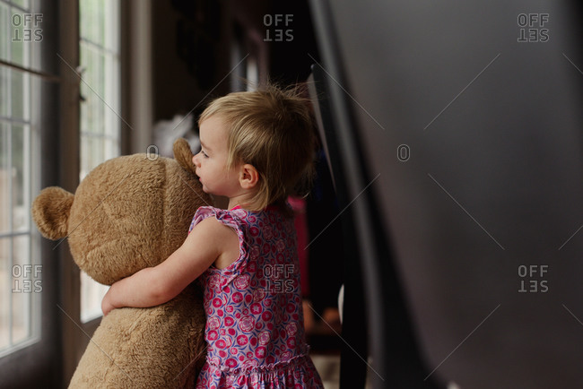 A little girl hugs a huge teddy bear