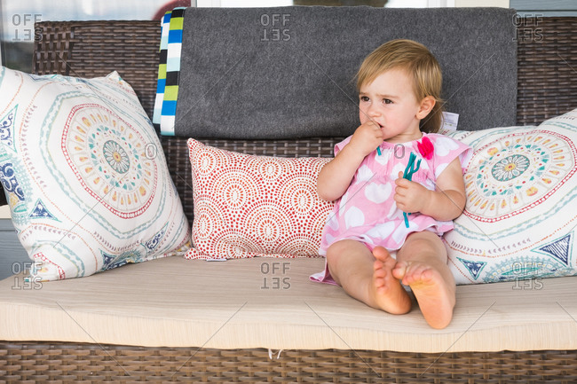 A little girl sits on a wicker couch eating gummy candy