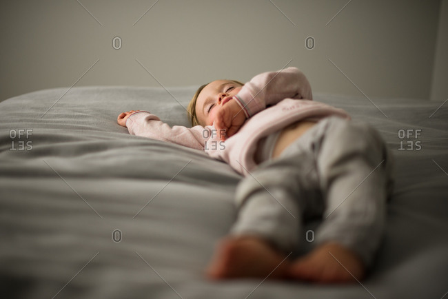 A little girl naps on a bed