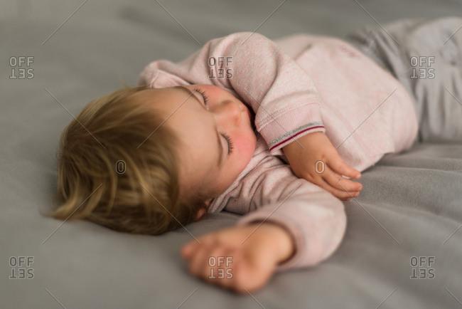 A little girl sleeps on a gray blanket