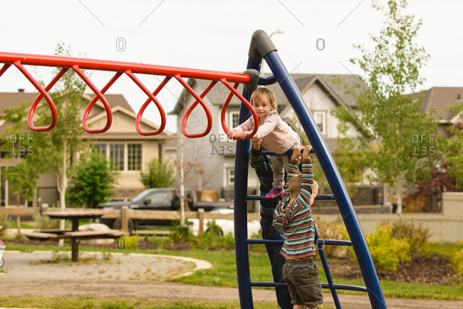 Siblings climb a playground structure