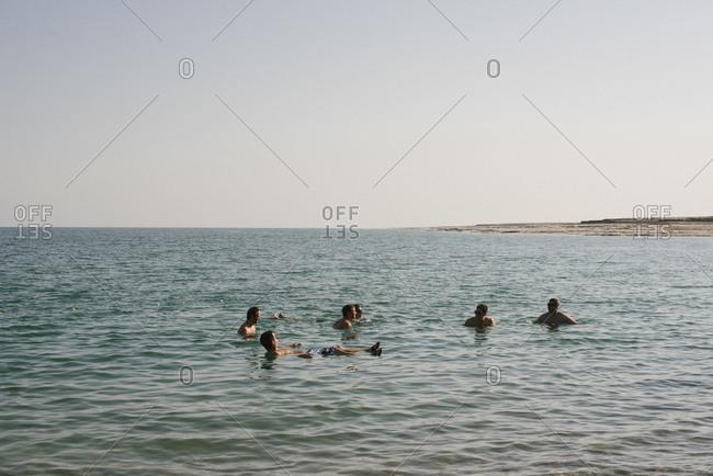 Israel - January 21, 2013: Six men floating in the saline waters of the Dead Sea