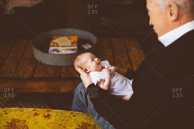 A grandfather holds his granddaughter
