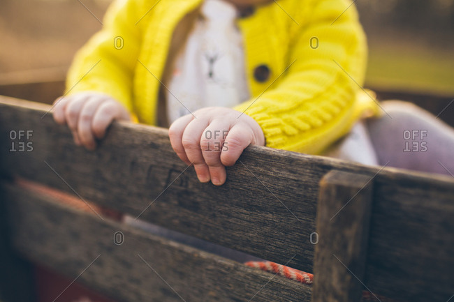 A baby in a yellow sweater rides in a wagon