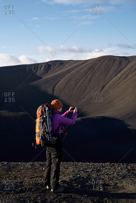 Woman on vacation in Iceland takes pictures while hiking