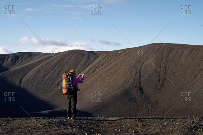 Woman on vacation in Iceland takes photos while hiking