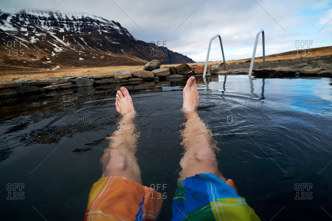 Tourist relaxing in an Icelandic natural geothermal pool