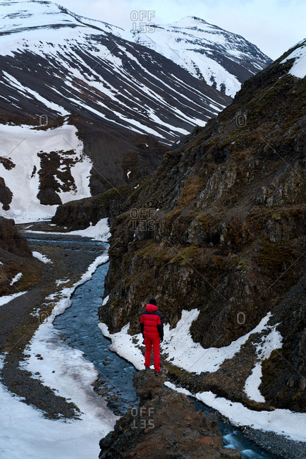 Hiker looking out at a canyon stream during winter in Iceland