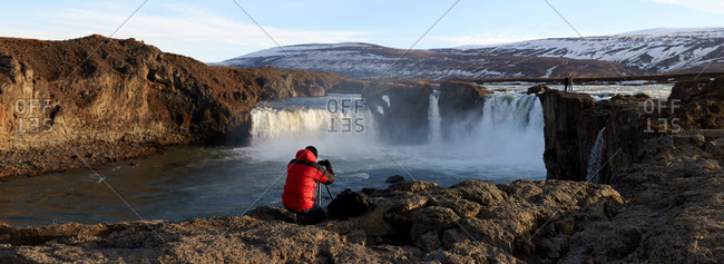 Photographer taking pictures of waterfalls in Iceland