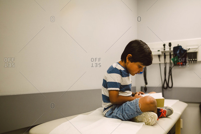 Boy reading book on exam table at doctor's office