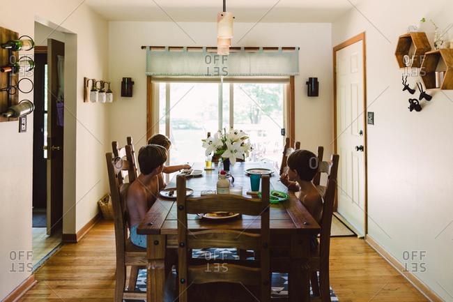 Three boys eating breakfast at dining room table