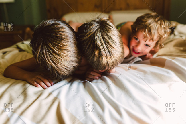 Three boys playing on a bed