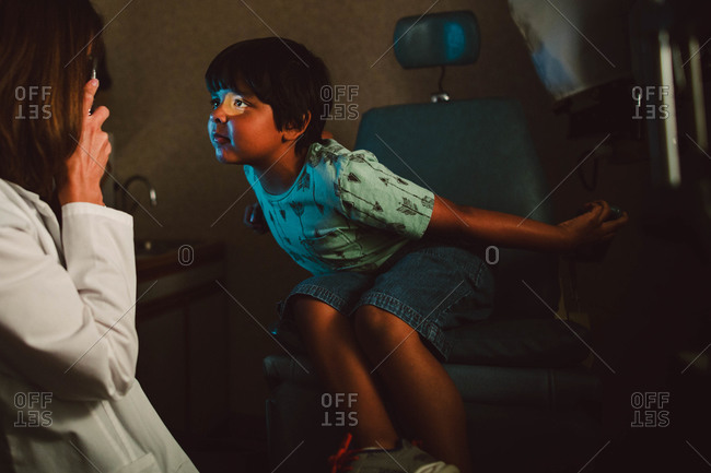 Young boy having eye exam performed by optometrist