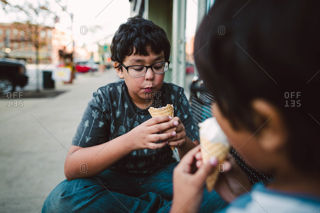 Two young boys eating ice cream on a bench