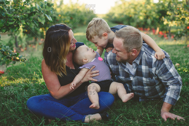 Family sitting together in an apple orchard