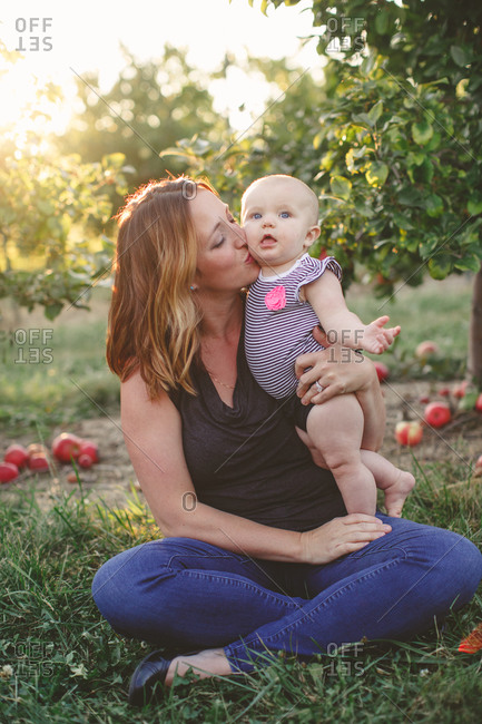 Mother holding infant daughter and kissing her cheek in an orchard